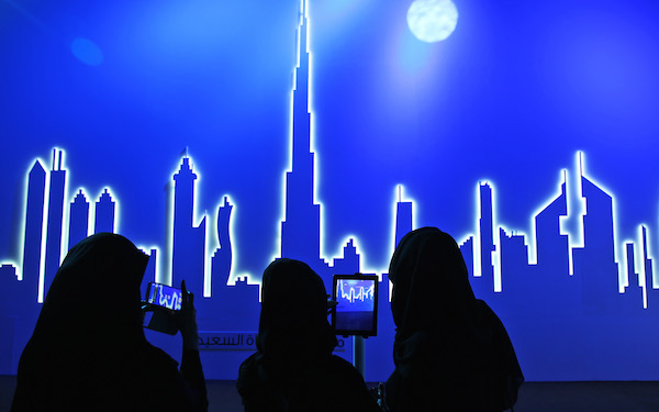 Emirati women snapping photos of the Dubai skyline.
